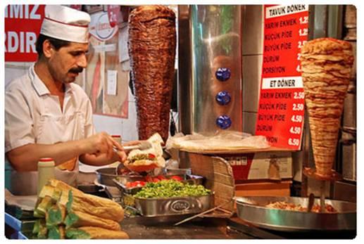 ¿Un taquero mexicano y bigotón? ¡No! Ve bien: es un turco preparando un kebab o sandwich griego.